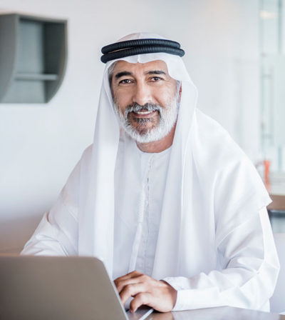 Businessman working in office with laptop computer wearing traditional Arabian agal and ghoutra.